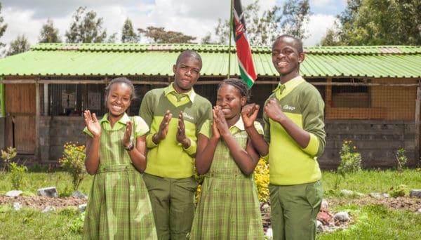 Kenyan school pupils stand outside Bridge school with Kenyan flag
